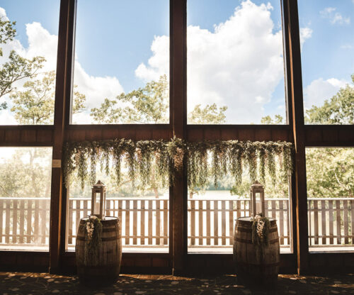Rustic wedding setup in front of large window with the sun shining through