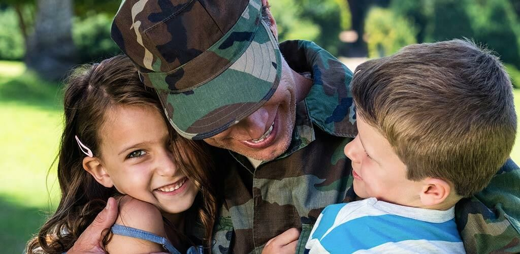 Service Member hugging children